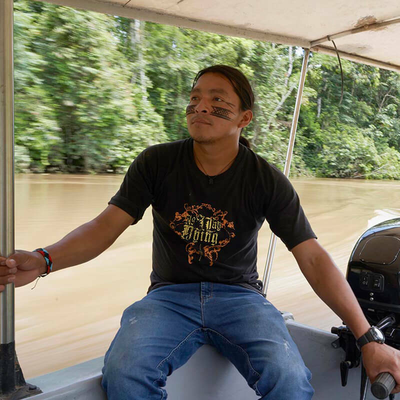 A man with traditional face painting steers a motor boat through a river