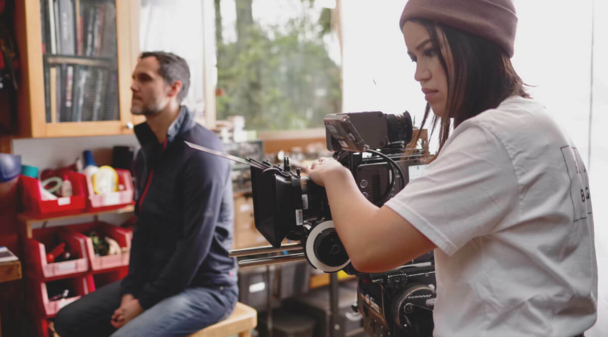 A young person, Asia Youngman,  holds a large camera filming while a man sits in behind her