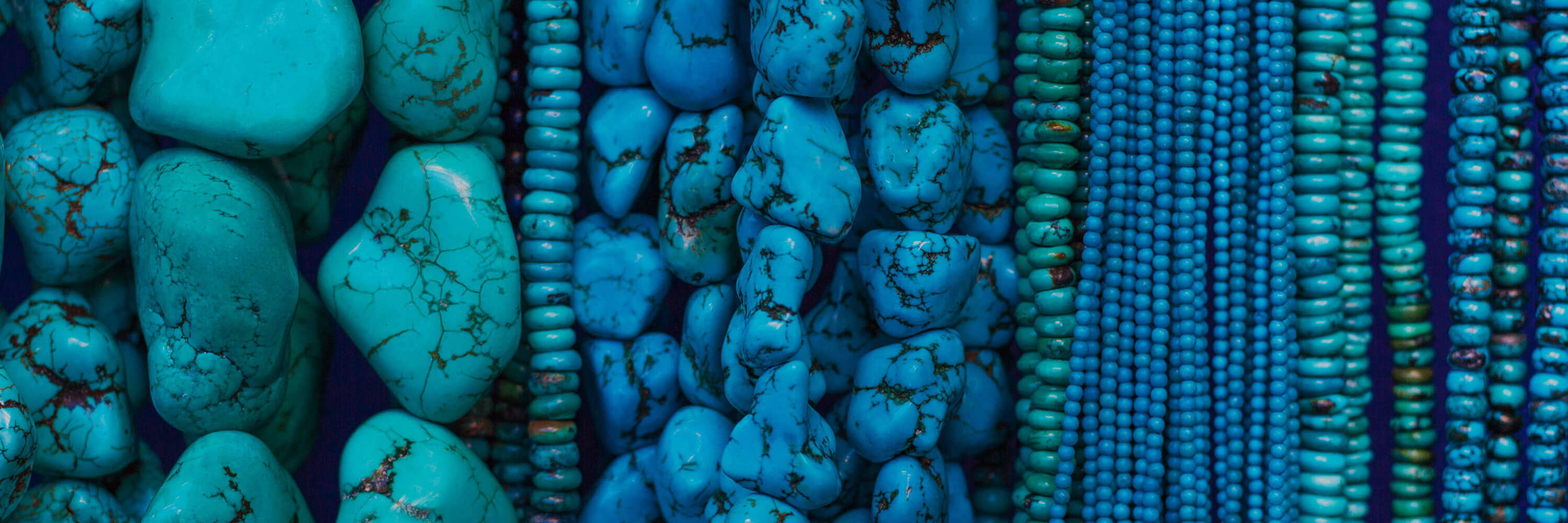 Several strings of blue and turquoise beads in various sizes