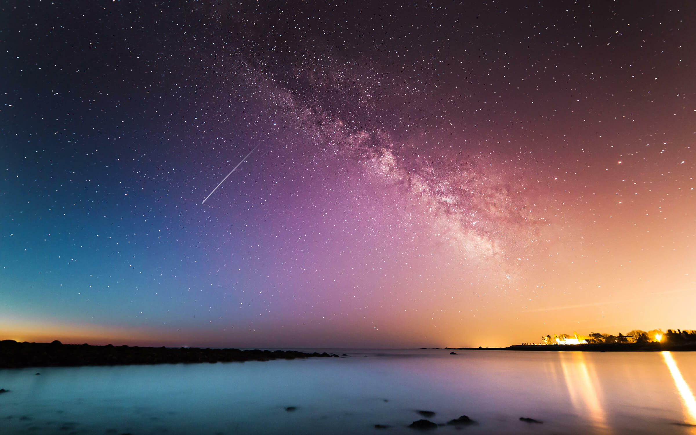 Colorful starry sky over water and land