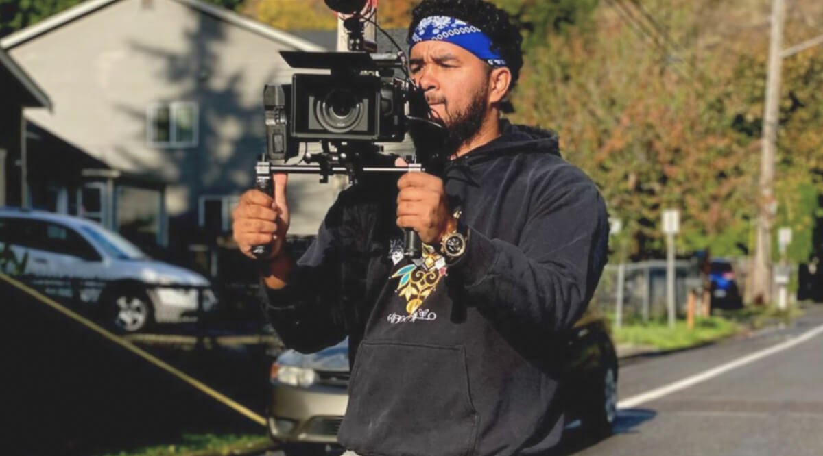A man, Chard Charlie, stands with a large camera on his shoulder filming in a suburban area in front of houses and cars
