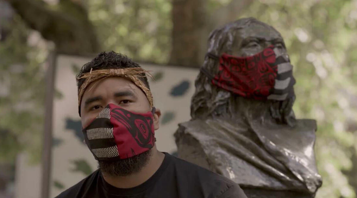Chad Charlie standing in front of a statue, each wearing the same mask