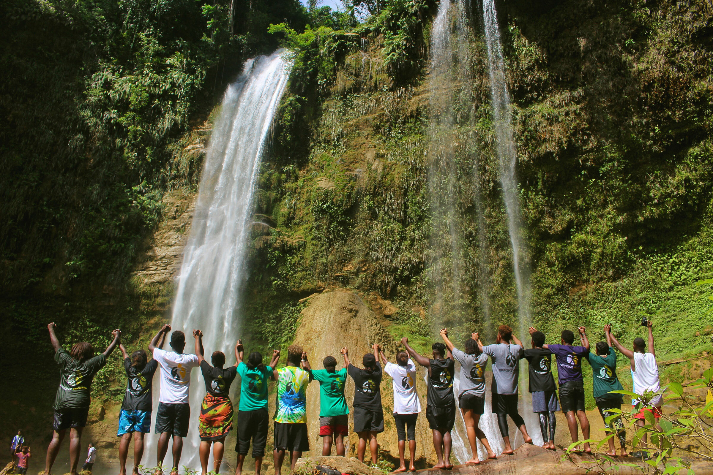 Group of people with hands held high facing a waterfall