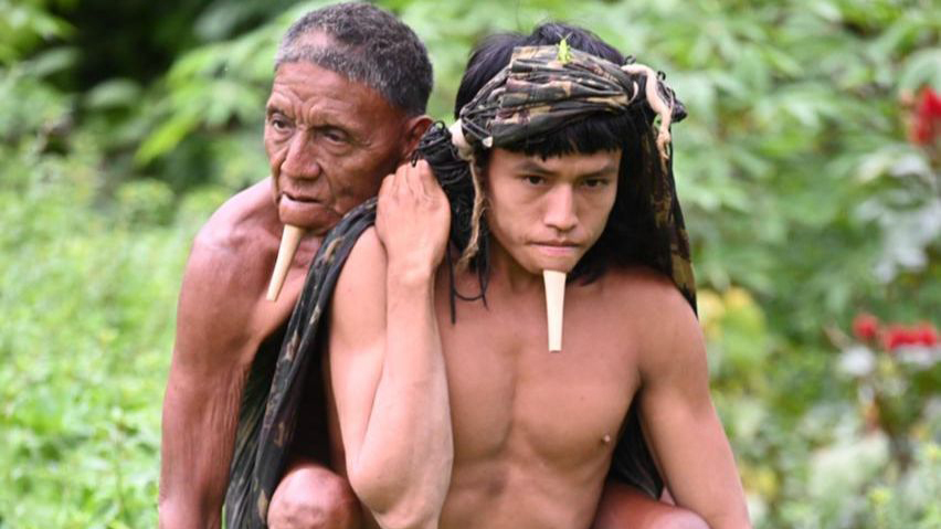 A young man carries an elder on his back through the jungle