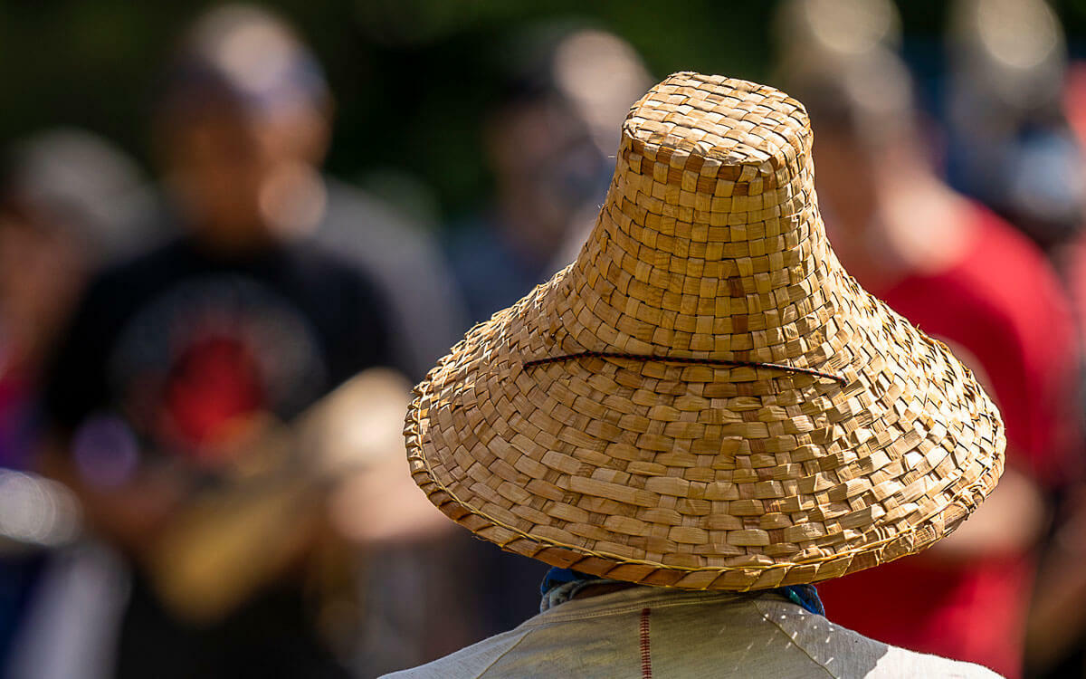 Back view of a person wearing a cedar hat with blurred people in the background