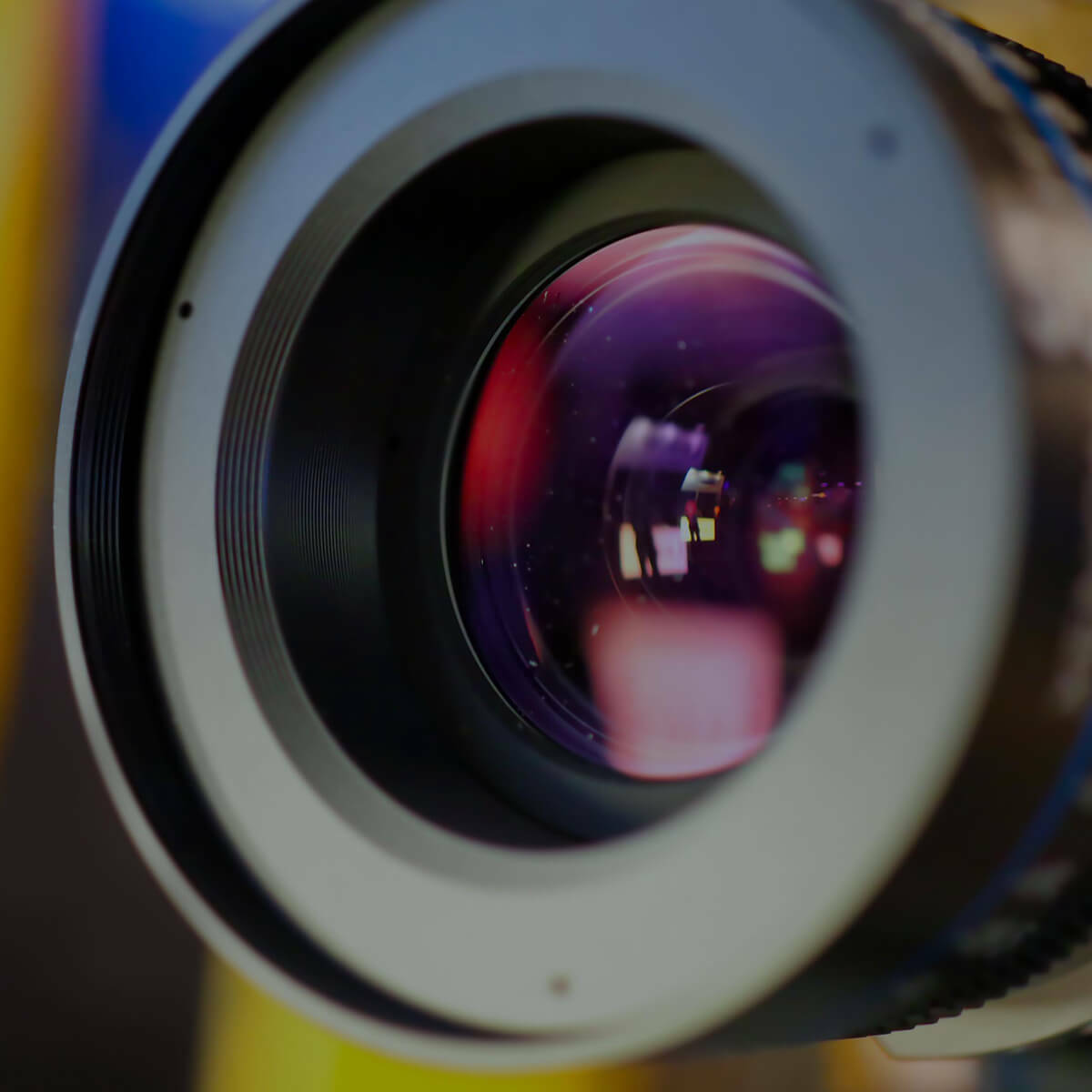 A close up of a camera lens with purple glare and reflection of a persons silhouette