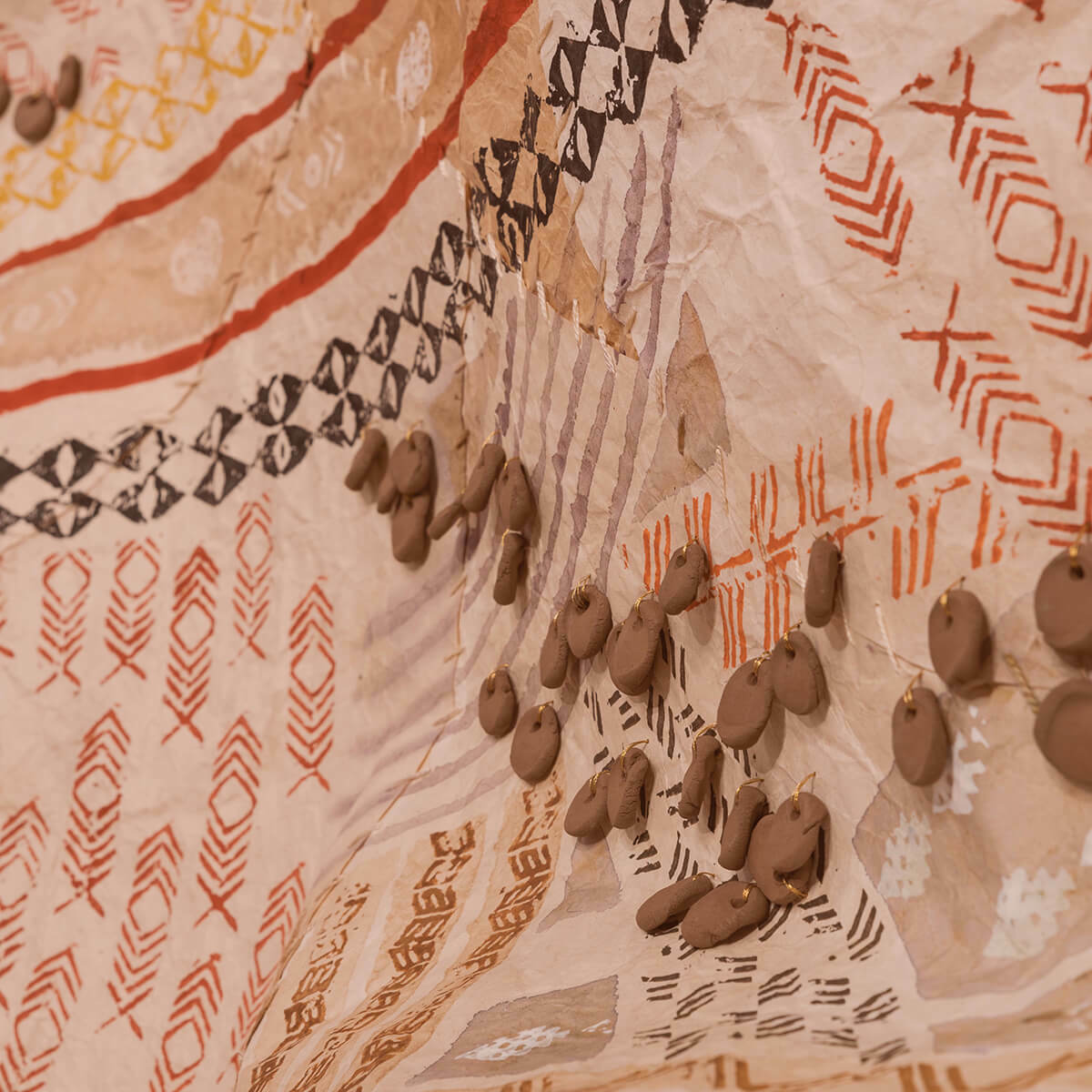 Close up view of  tan tapestry with red and brown pattern detailing and brown beading attached