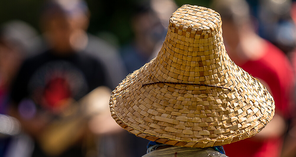 A silhouette of a man in a woven hat stands in front of a crowd of people