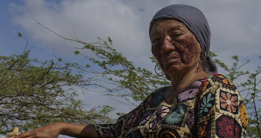Native woman with bandana looks into camera
