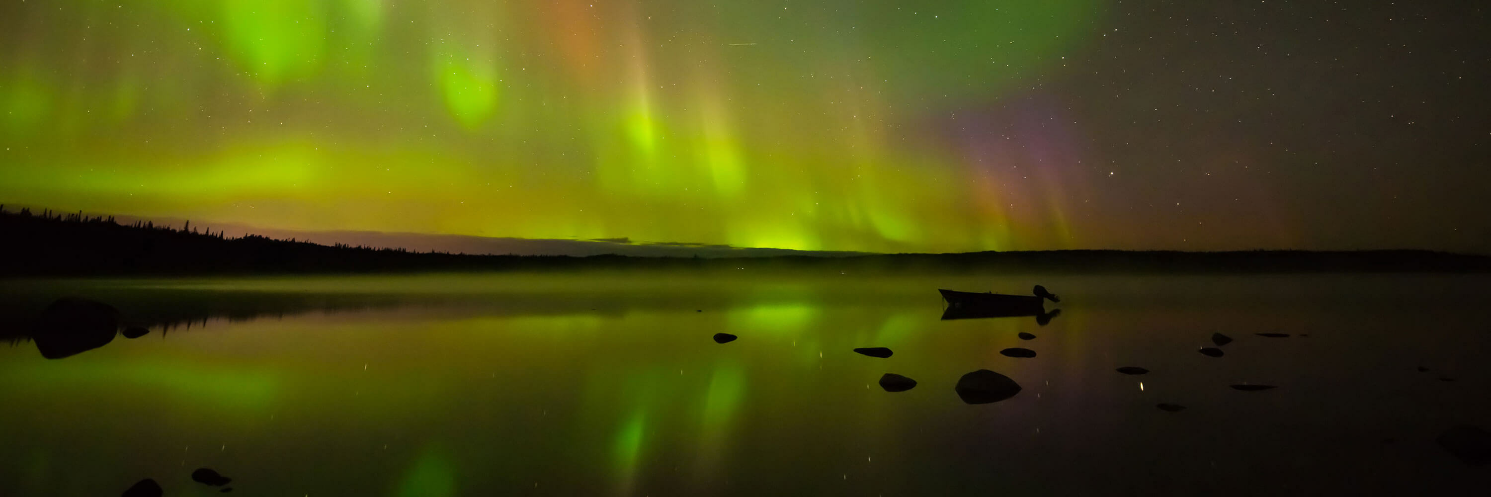 Colorful green aurora over land, water, and boat