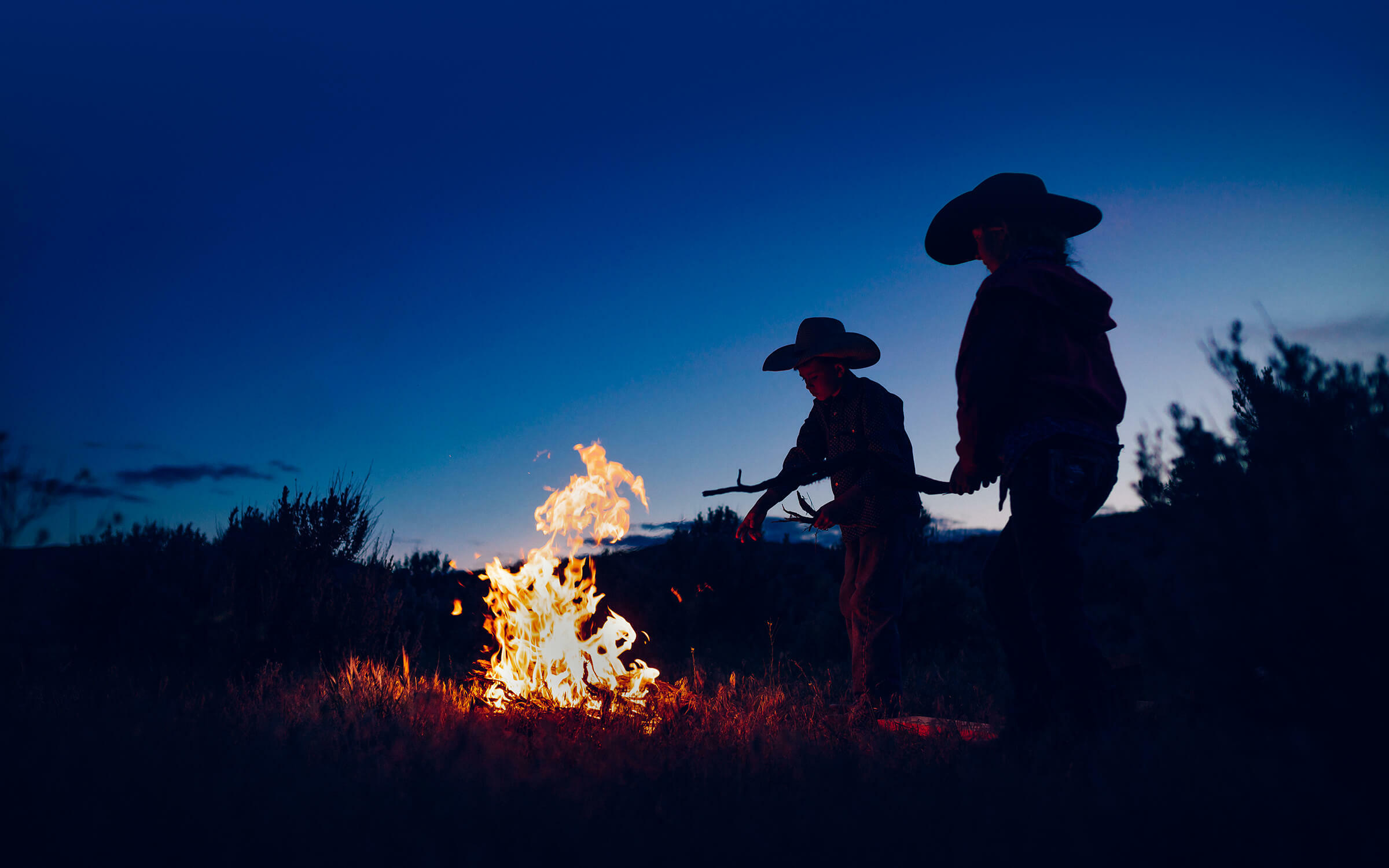 Two kids with cowboy hats tending a fire