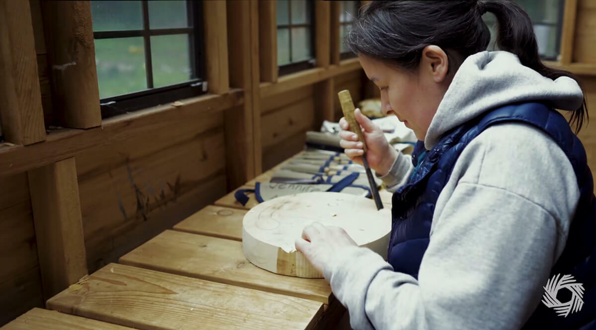 Portrait of a women using chisel to do wood work on a round block