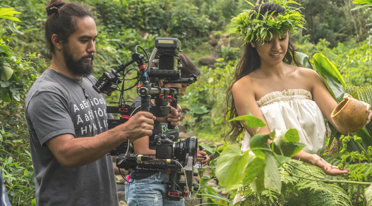 A man, Justyn ah Chong, uses camera to film a women pouring water over plants in traditional dress