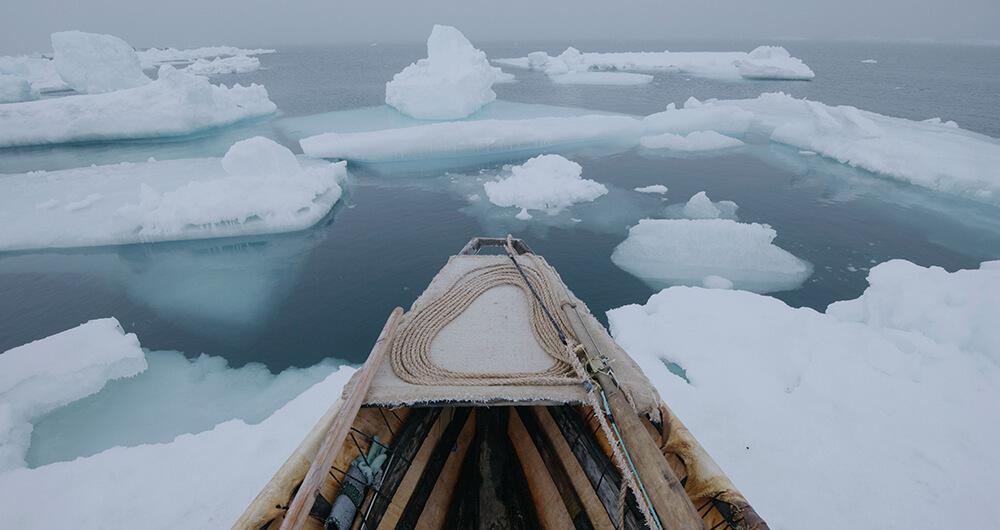 Kayak facing water with icebergs