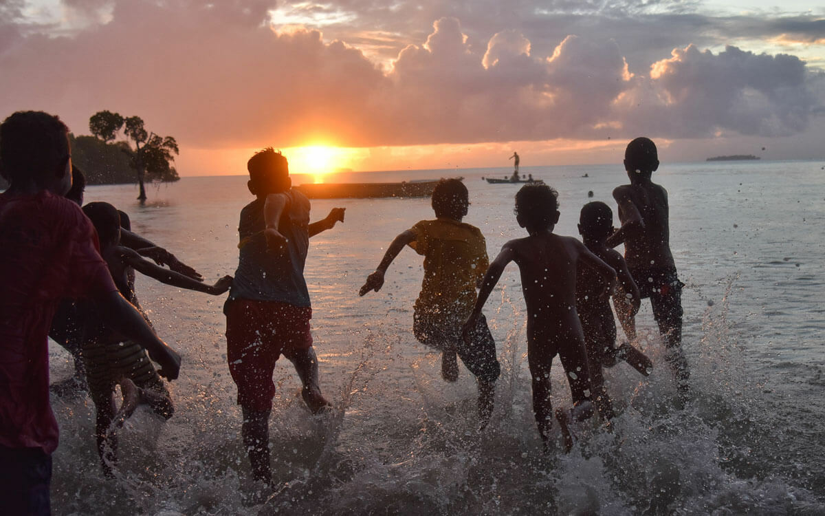 Children running into water with a sunset in the background