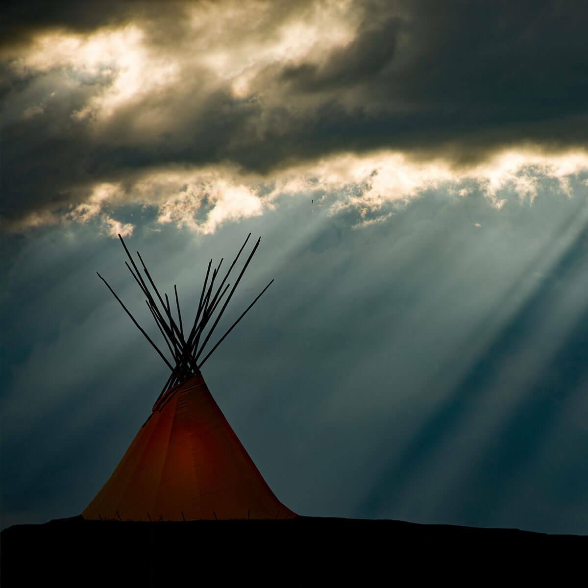 Tepee under a cloud filled sky
