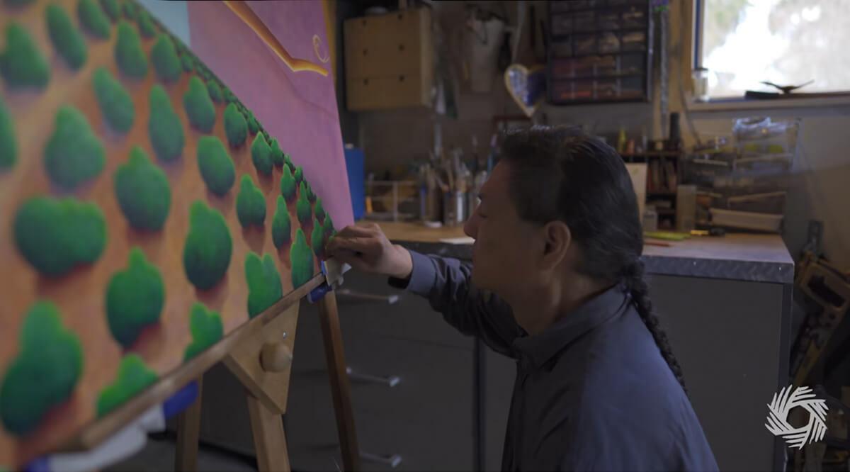 Male Artist Linley b Logan paints green bushes on a large canvas
