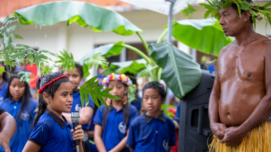 A young girl speaks into a microphone of front of other children and a man in head dress and grass skirt