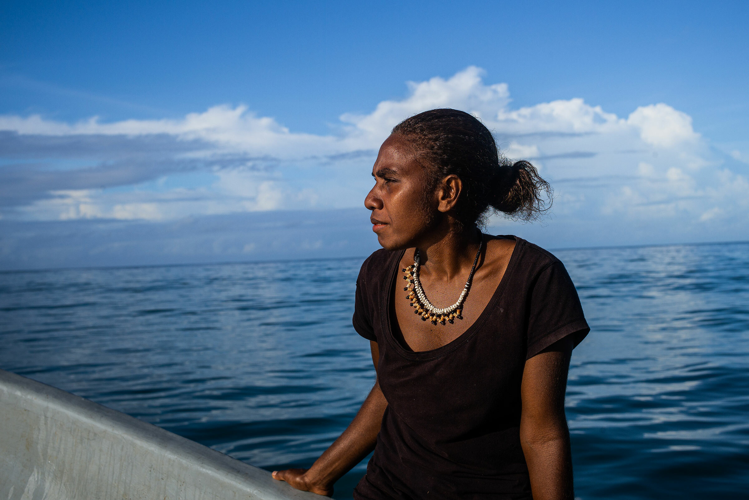 A woman staring into the distance in front of water