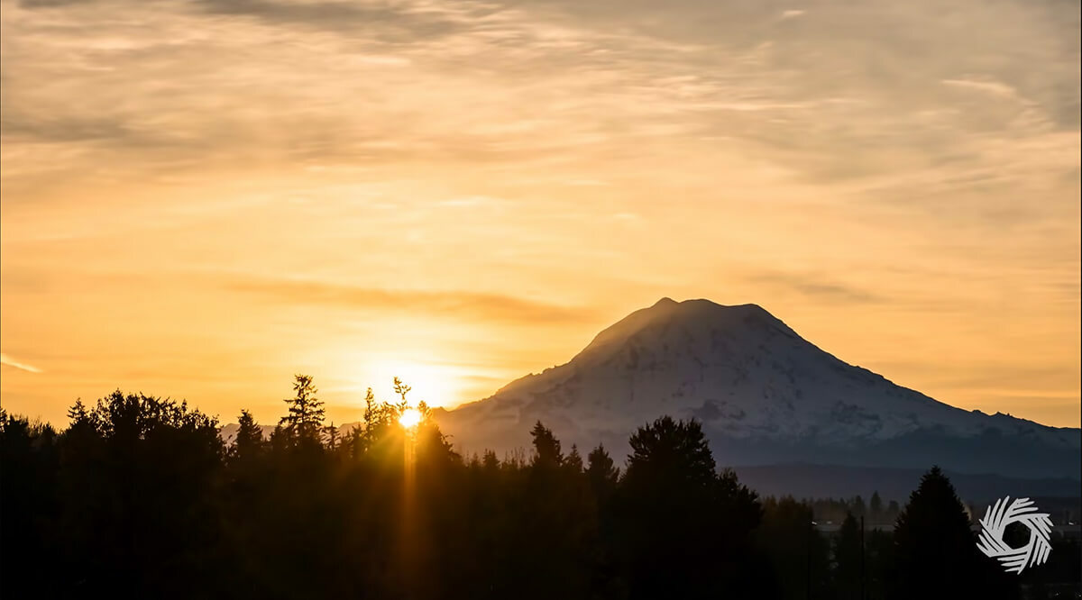 Sun rising behind a mountain and silhouette of trees