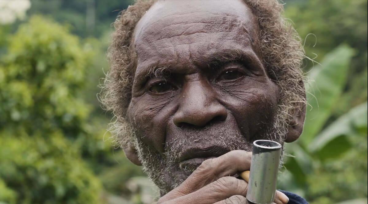 Man smoking a pipe looking into camera