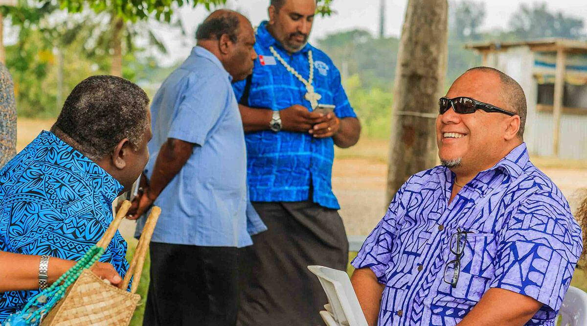 Group of men in Hawaiian shirts chatting