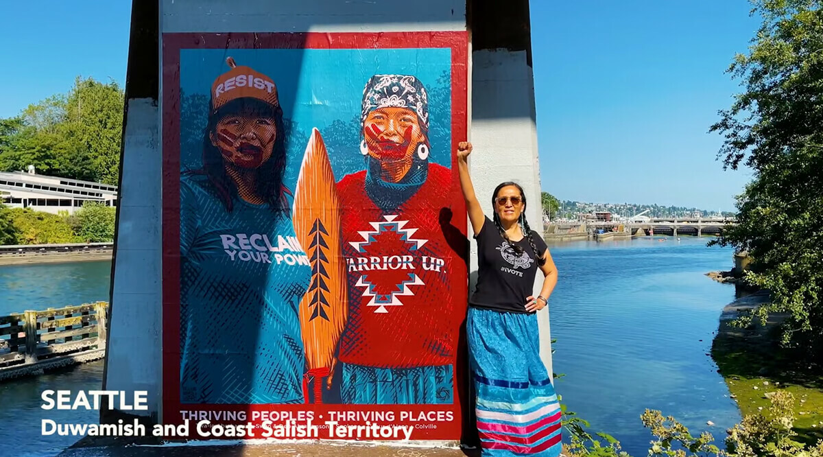 Women standing with first raised next to painting on a pillar next to a river with two people in indigenous face paint and slogan t-shirts