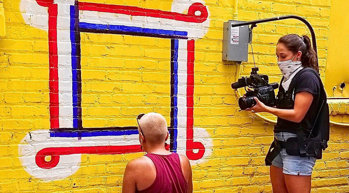 Woman taking video of another painting a brick wall