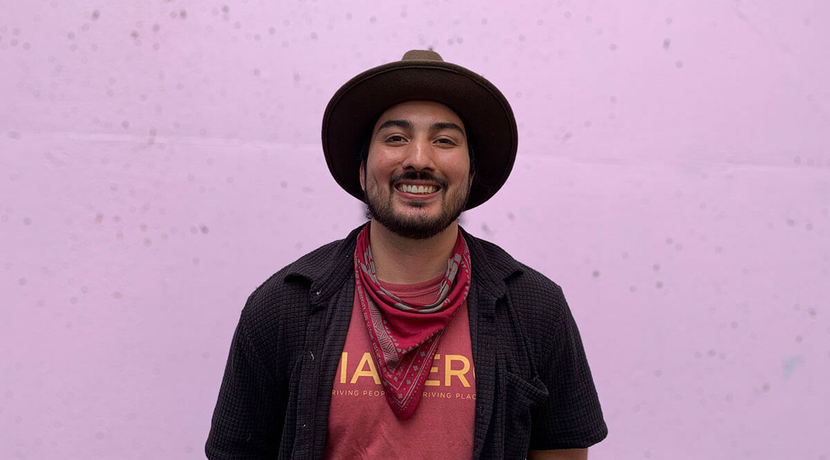 Portrait of a man in a hat standing in front of a pink wall