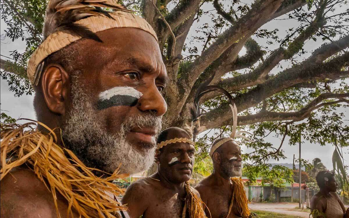 Tribespeople with painted faces and a tree in the background