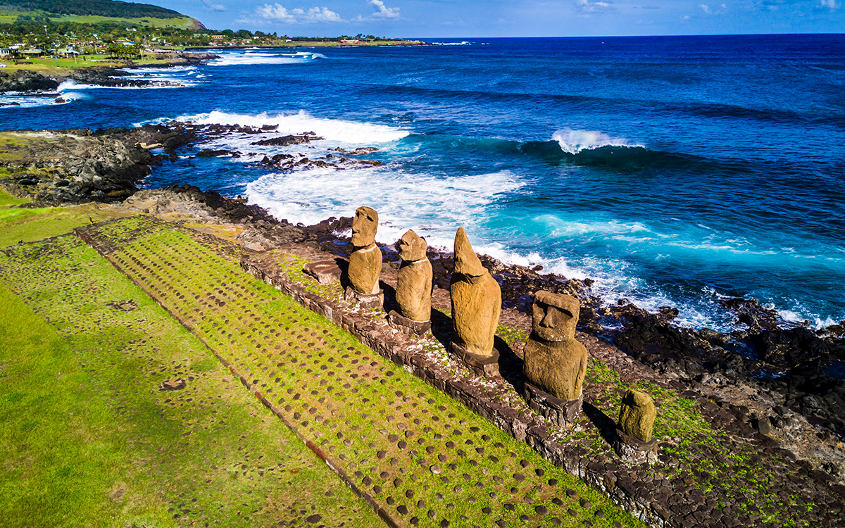 Five ancient statues in line across a cliff with crashing waves and a village in the background