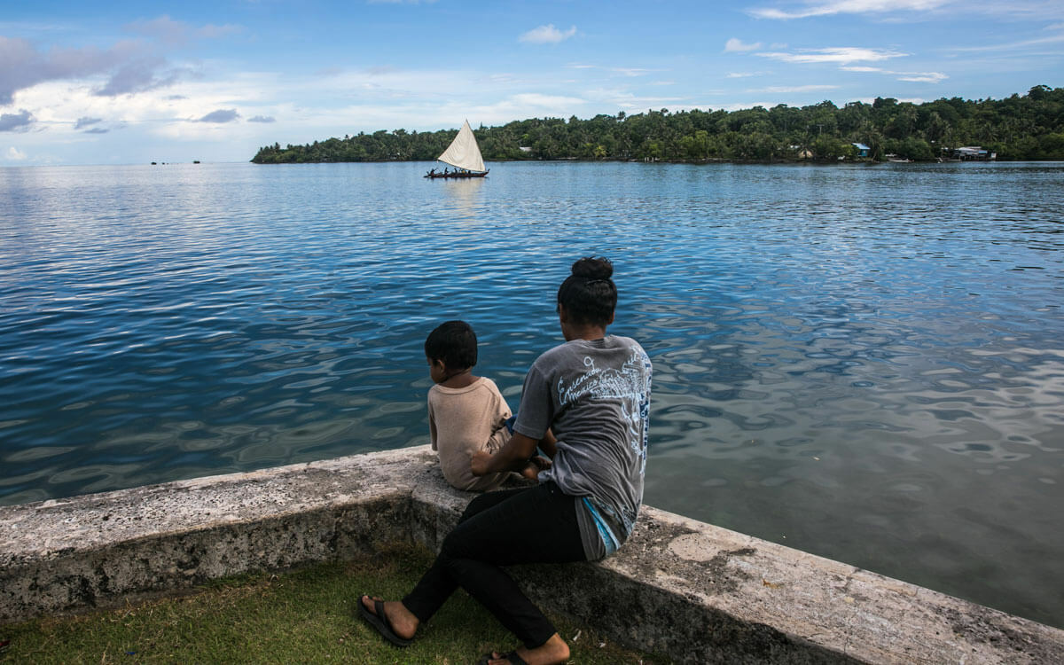 Woman with a small child looking out water with a small boat and island in the background