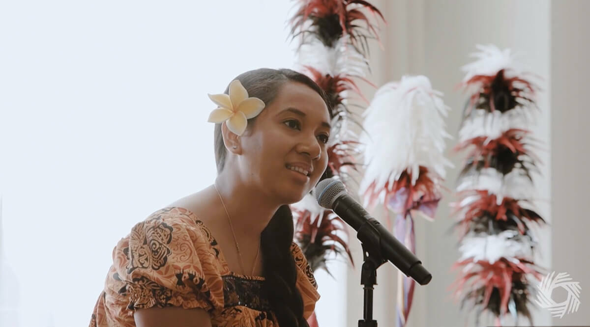Portrait of a woman, Yolanda Joab Mori, sitting in front of a window next to plants, speaking into a microphone